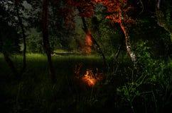 Silhouette étrange dans une forêt fantasmagorique foncée la nuit, lumières surréalistes de paysage mystique avec l'homme rampant photographie stock