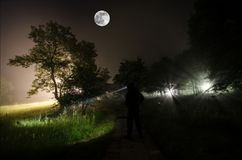 Silhouette étrange dans une forêt fantasmagorique foncée la nuit, lumières surréalistes de paysage mystique avec l'homme rampant image stock