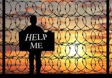 Silhouette беженец с плакатом прося помощь Стоковое фото RF