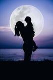 Silhouette взгляд со стороны матери и ребенка наслаждаясь с большим moo Стоковая Фотография