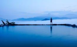 Silhouette вид сзади молодой женщины стоя около бассейна для изумительного ландшафта голубого неба и гор в тумане утра стоковые фотографии rf