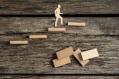 Silhouette вырезы человека идя вверх по деревянным шагам Стоковые Изображения RF