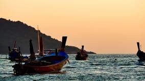 Silhouette группа в составе шлюпка длинного хвоста convertedfloating в море andaman с золотым светом сток-видео