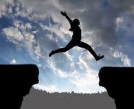 Silhouette девушка скача над зазором Стоковые Изображения RF