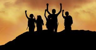 Silhouette дети при оружия поднятые на холме против неба во время захода солнца Стоковая Фотография