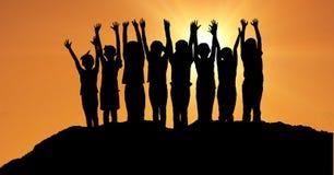Silhouette дети при руки поднятые на холме против оранжевого неба Стоковые Изображения