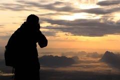 Silhouette женщина на верхней горе в утре Стоковые Фото