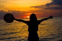 Silhouette женщины наслаждаясь красивым заходом солнца на пляже Стоковые Фото