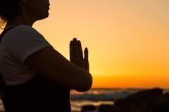 Silhouette йога молодой женщины практикуя на пляже на заходе солнца Стоковые Изображения