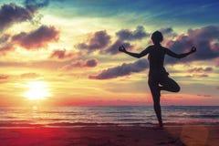 Silhouette йога молодой женщины практикуя на пляже на сюрреалистском заходе солнца Стоковые Фотографии RF