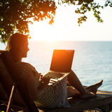 Silhouette компьтер-книжка c девушки сидя на lounger около моря в заходе солнца Стоковая Фотография RF