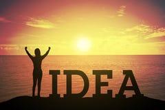 Silhouette молодая женщина стоя и поднимая вверх ее рука о концепции победителя на тексте ИДЕИ стоковое фото rf