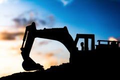 silhouette отслеживаемые песок экскаватора и предпосылка камня и неба стоковые фото