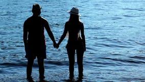 Silhouette пары держа руки на заходе солнца на пляже акции видеоматериалы