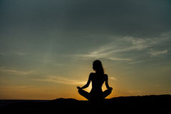 Silhouette положение лотоса девушки раздумья на камне на предпосылке сногсшибательного моря Стоковая Фотография RF