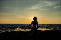 Silhouette положение лотоса девушки раздумья на камне на предпосылке сногсшибательного моря Стоковое фото RF
