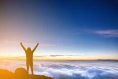 Silhouette руки женщины поднимая на горе на утре с облаком Стоковые Фото