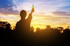 Silhouette руки поднятые женщиной держа бутылку на небе, стоковое изображение rf