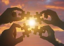 Silhouette 4 руки пробуя соединить часть головоломки с предпосылкой захода солнца стоковые фото