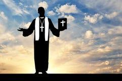 Silhouette священник с библией в его руке Стоковые Изображения