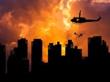silhouette солдаты rappelling вниз от вертолета на небоскребе здания в заходе солнца Стоковые Изображения