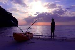 Silhouette сплавляться на пляже при туристская девушка смотря заход солнца голубого неба Стоковые Фото