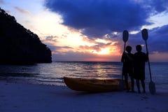 Silhouette сплавляться на пляже при туристская девушка смотря заход солнца голубого неба Стоковая Фотография