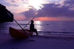 Silhouette сплавляться на пляже при туристская девушка смотря заход солнца голубого неба Стоковое Фото