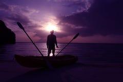 Silhouette сплавляться на пляже при человек смотря заход солнца Стоковое фото RF