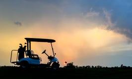 Silhouette тележка гольфа в поле для гольфа с красочной twilight предпосылкой неба Стоковое Фото