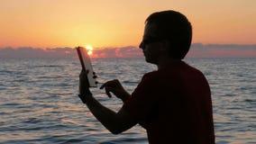 Silhouette человек с цифровой таблеткой в руках на пляже захода солнца Солнце почти установлено за океаном акции видеоматериалы