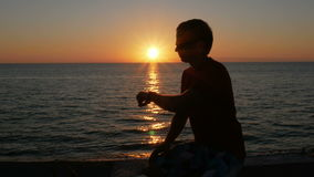 Silhouette человек с smartwatch в наличии на пляже захода солнца Он касается умным вахтам и проверяется сообщение Солнце акции видеоматериалы