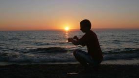 Silhouette человек с smartwatch в наличии на пляже захода солнца Он касается умным вахтам и проверяется сообщение Солнце видеоматериал