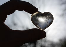 Silhouette. Of hand holding heart shaped glass Stock Images