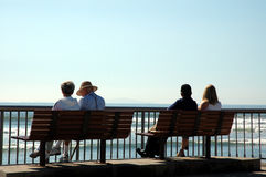 Silhouette of 4 people. 4 people sitting on a bench looking at the beach royalty free stock photography