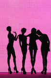 Silhouette 4 women. Silohuette of four women standing with pink colored background Stock Photo