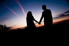 пары предпосылки silhouette детеныши захода солнца Стоковые Изображения