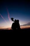 пары предпосылки silhouette детеныши захода солнца Стоковое Изображение