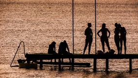 Silhouette of 6 Person on Dock Near the Calm Body of Water Royalty Free Stock Photos