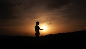 Silhouette. Photo of a woman holding sun in hand Royalty Free Stock Photo