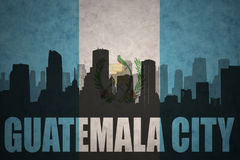 Silhouette abstraite de la ville avec le texte Guatemala City au drapeau de Guatémaltèque de vintage Photo stock