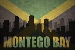Silhouette abstraite de la ville avec le texte Montego Bay au drapeau jamaïcain de vintage Images libres de droits