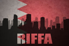 Silhouette abstraite de la ville avec le texte Riffa au drapeau du Bahrain de vintage Photographie stock libre de droits