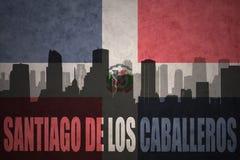 Silhouette abstraite de la ville avec le texte Santiago de los Caballeros au drapeau de la République Dominicaine de vintage Photographie stock