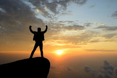 Silhouette achievements successful man is on top of hill. Silhouette achievements successful arm up man is on top of hill celebrating success with sunrise royalty free stock photo