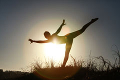 Silhouette of acrobatic teen gymnast balancing with the sun behi Royalty Free Stock Photos