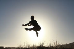 Silhouette of acrobatic teen gymnast jumping with the sun behind Royalty Free Stock Image