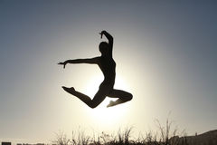 Silhouette of acrobatic teen gymnast jumping with the sun behind Royalty Free Stock Photos