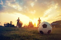 Silhouette action sport outdoors of a group of kids having fun playing soccer football for exercise in community rural area under. The twilight sunset sky stock image