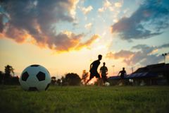 Silhouette action sport outdoors of a group of kids having fun playing soccer football for exercise in community rural area under. The twilight sunset sky royalty free stock image